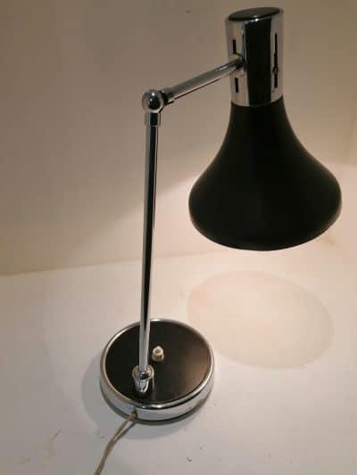 Vue éclairée de la lampe vintage au design scandinave des années 50/60 par ARNE JACOBSEN. Acier laqué noir et chrome. Orientable dans différentes positions par ses deux rotules. Vintage French Art | Brocante en ligne